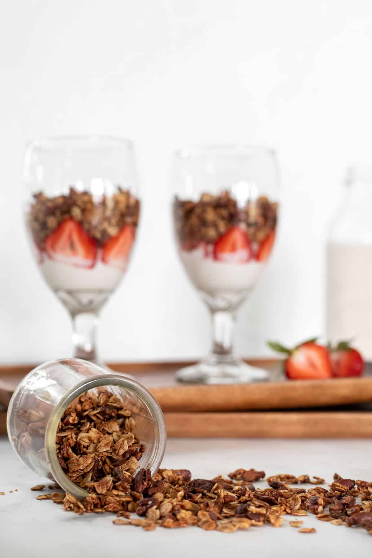 Granola in parfait glasses with yogurt and strawberries with a jar of granola spilled out in front of them.