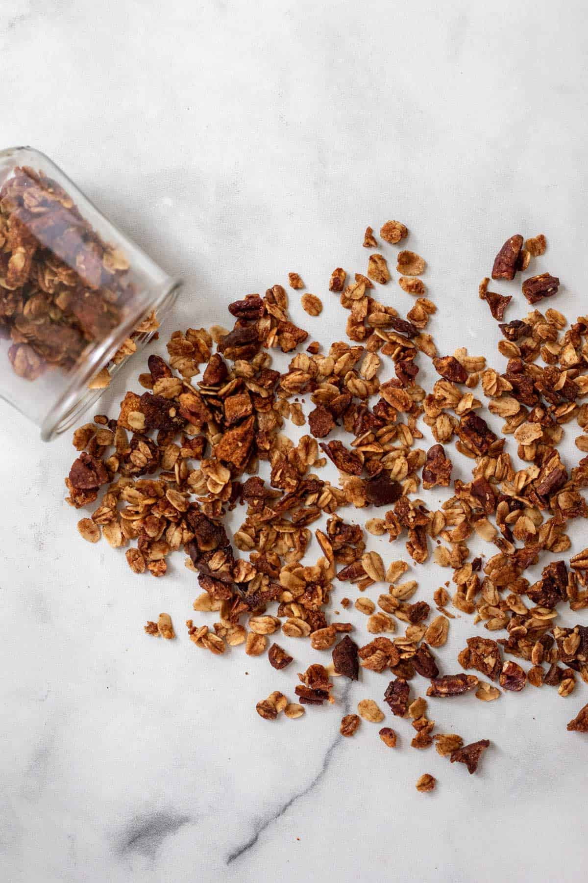 Baked granola spread spilled from a jar and spilled out across a white backdrop.