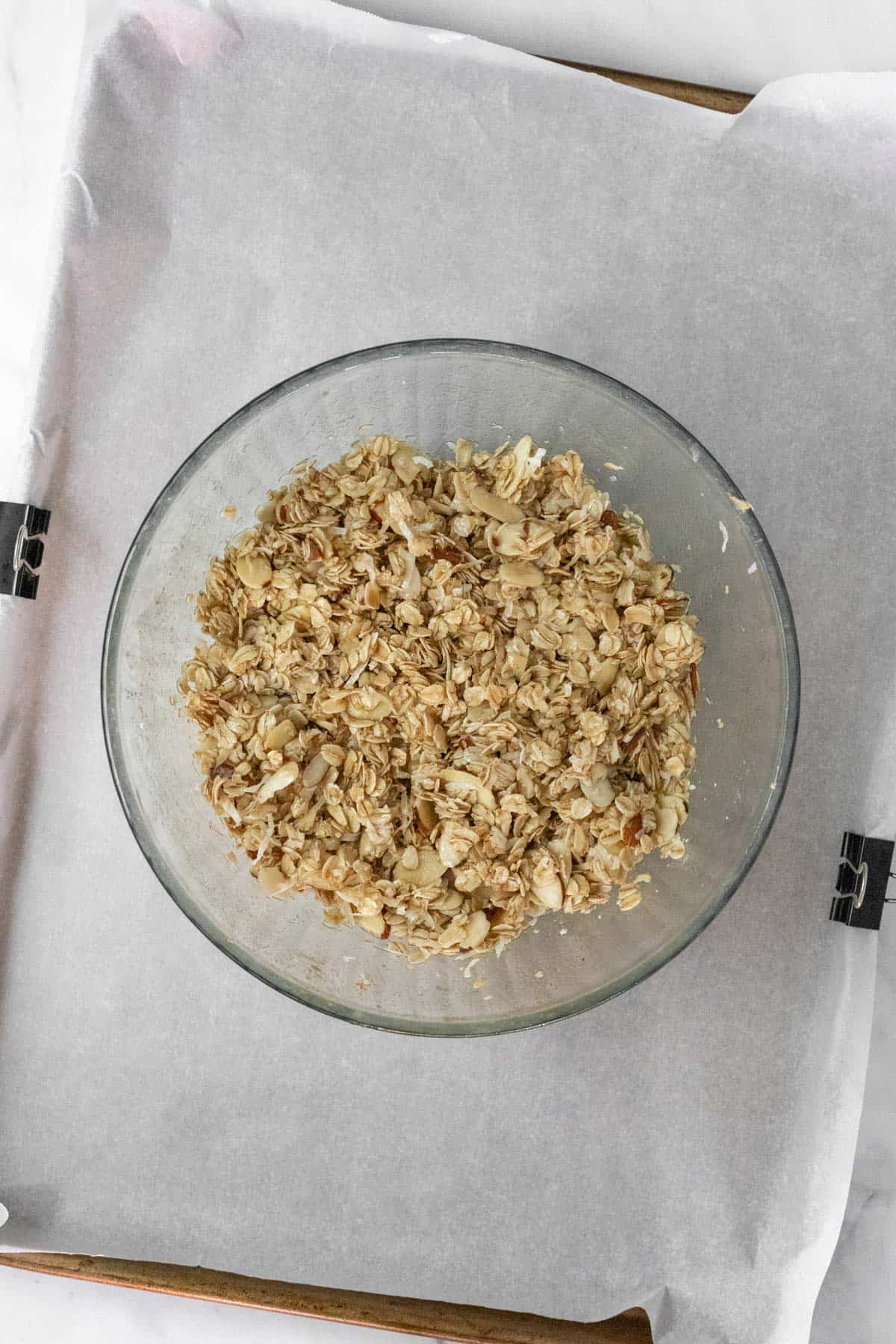Ingredients for homemade granola mixed together in a glass bowl.