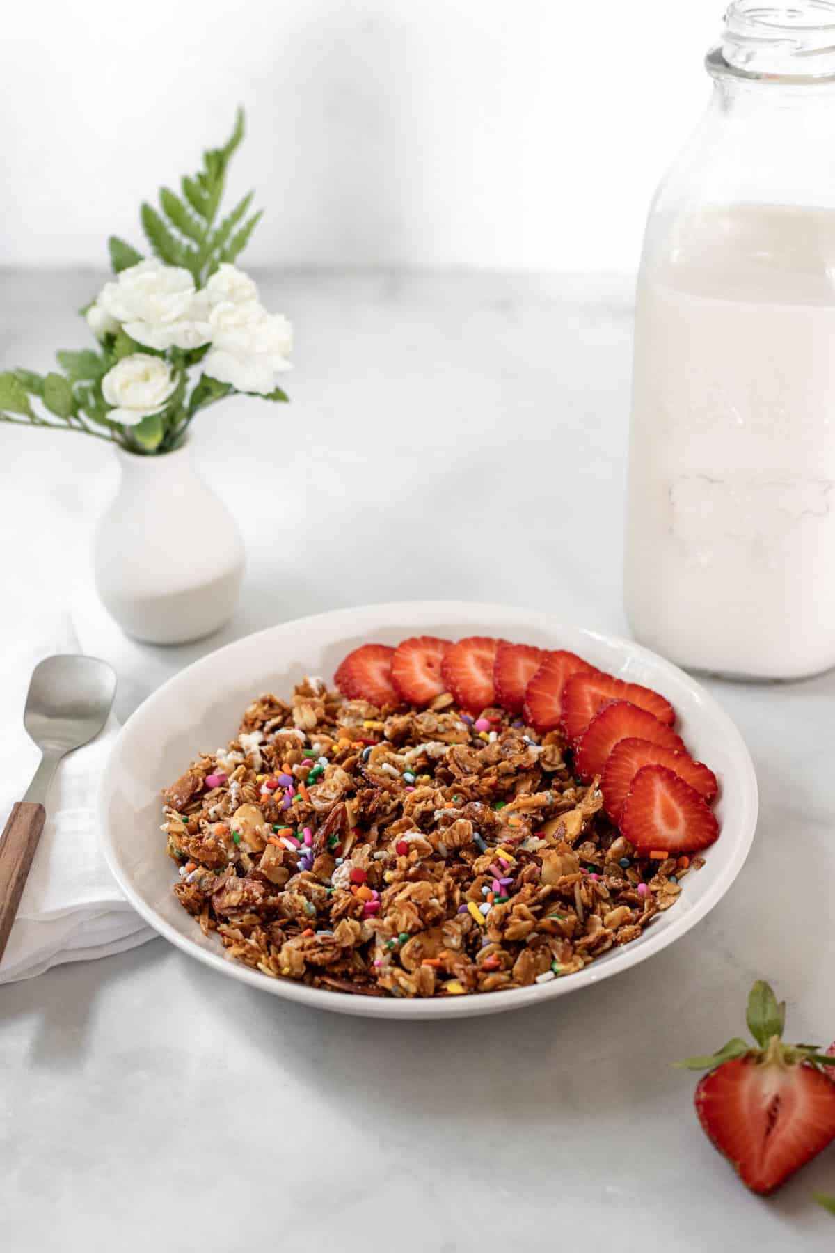 A bowl of vanilla almond granola with strawberries on top and a spoon, napkin, vase with white flowers, and jar of milk around it.