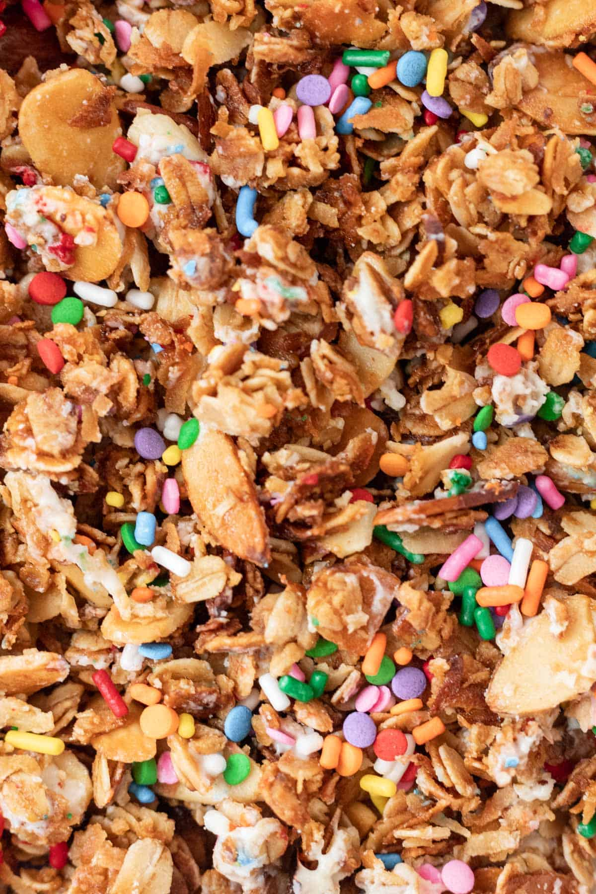 A closeup of baked granola with melted white chocolate and rainbow sprinkles.
