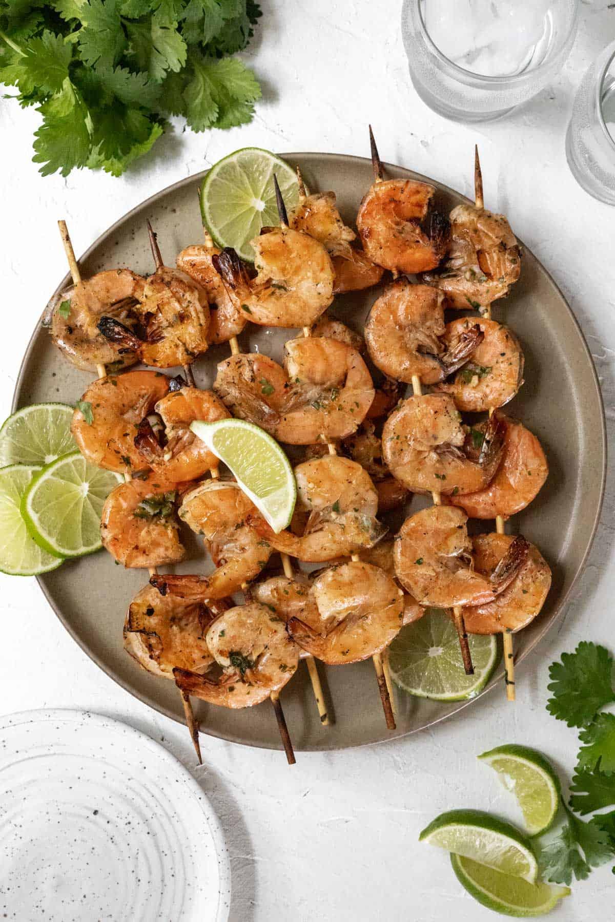 Grilled shrimp skewers garnished with limes on a beige plate.