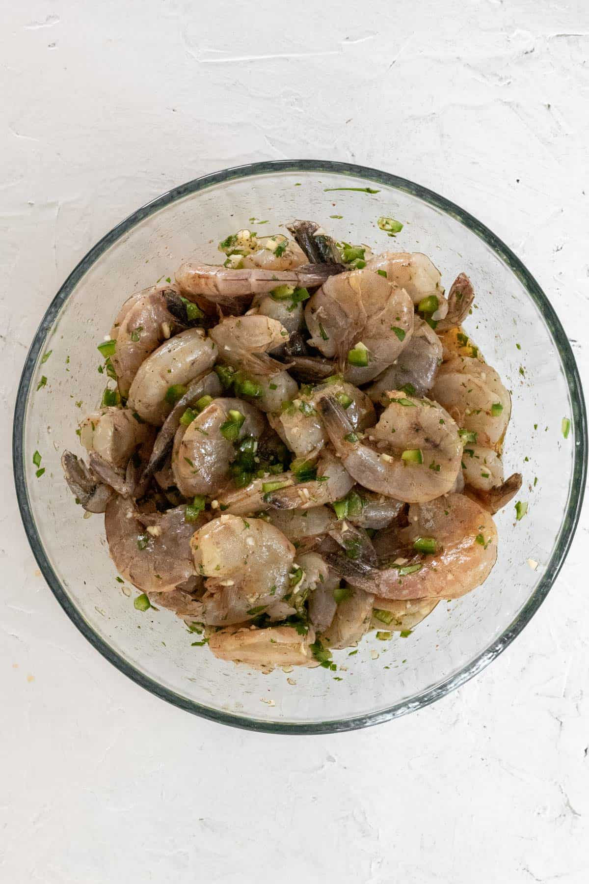 Raw shrimp mixed with the tequila lime marinade in a glass bowl.