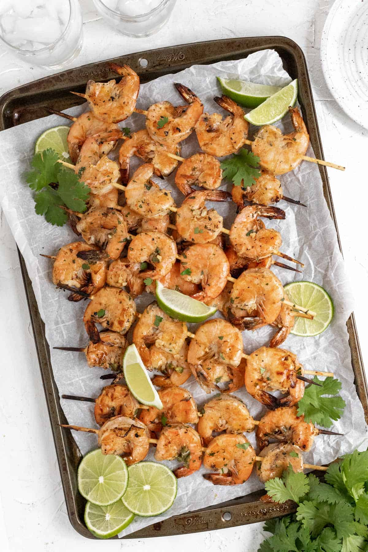 Grilled margarita shrimp skewers on a sheet pan with limes and cilantro.