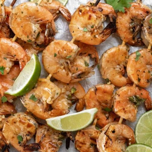 Grilled shrimp skewers garnished with limes and cilantro on a sheet pan.