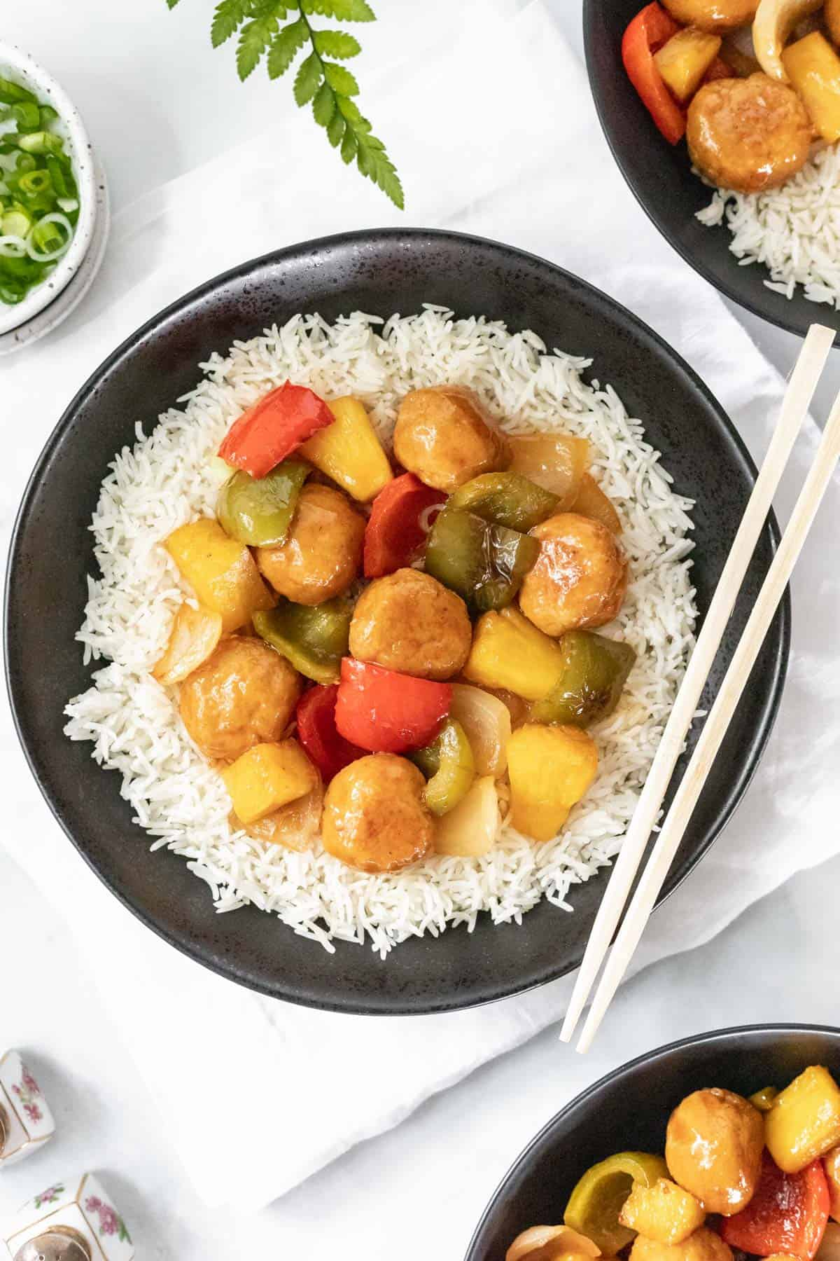Sweet and sour pineapple chicken meatballs on a bed of white rice in a black bowl with chopsticks.