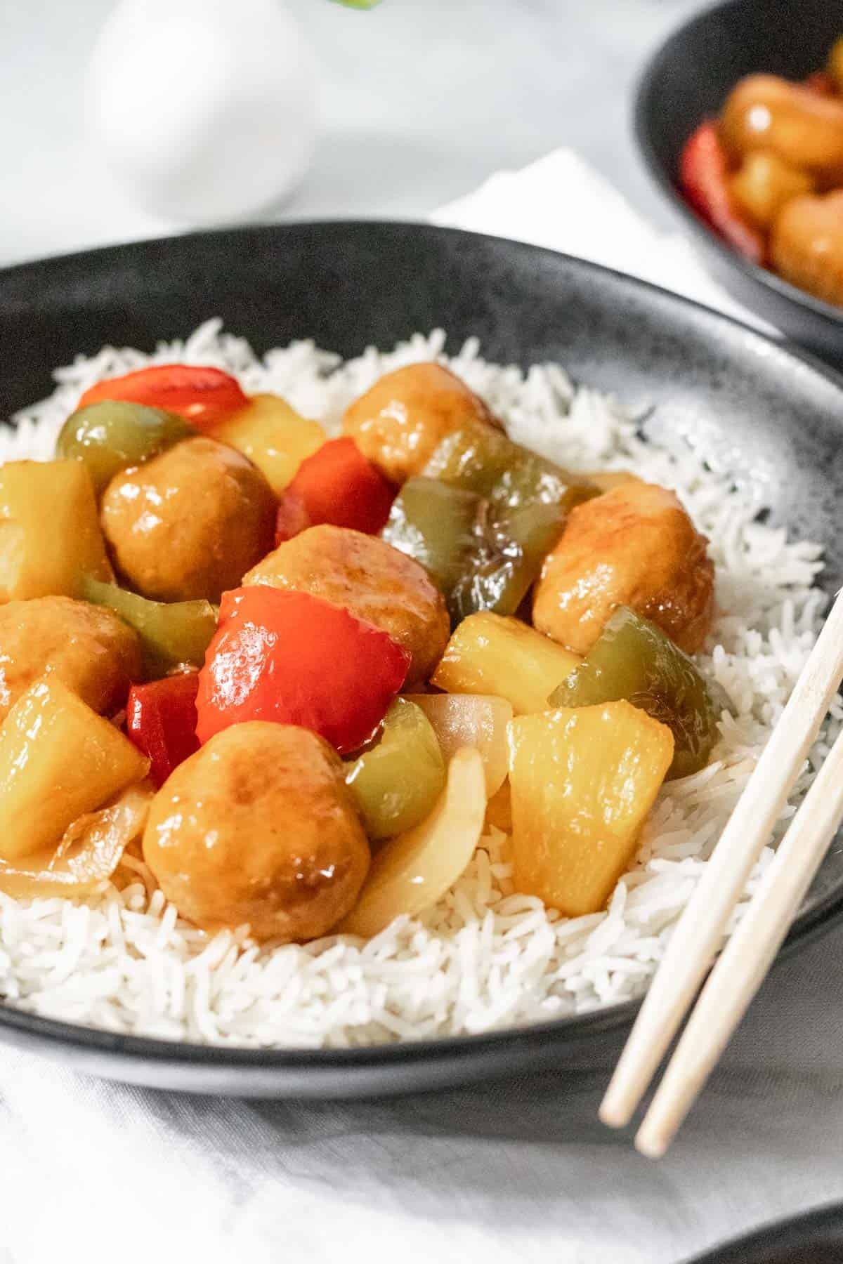 Sweet and sour chicken meatballs with stir fried peppers, onions, and pineapple on a bed of white rice.