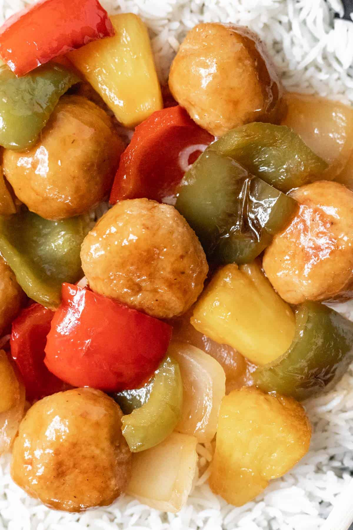A closeup of meatballs, peppers, pineapple, and onions glazed with sweet and sour sauce.