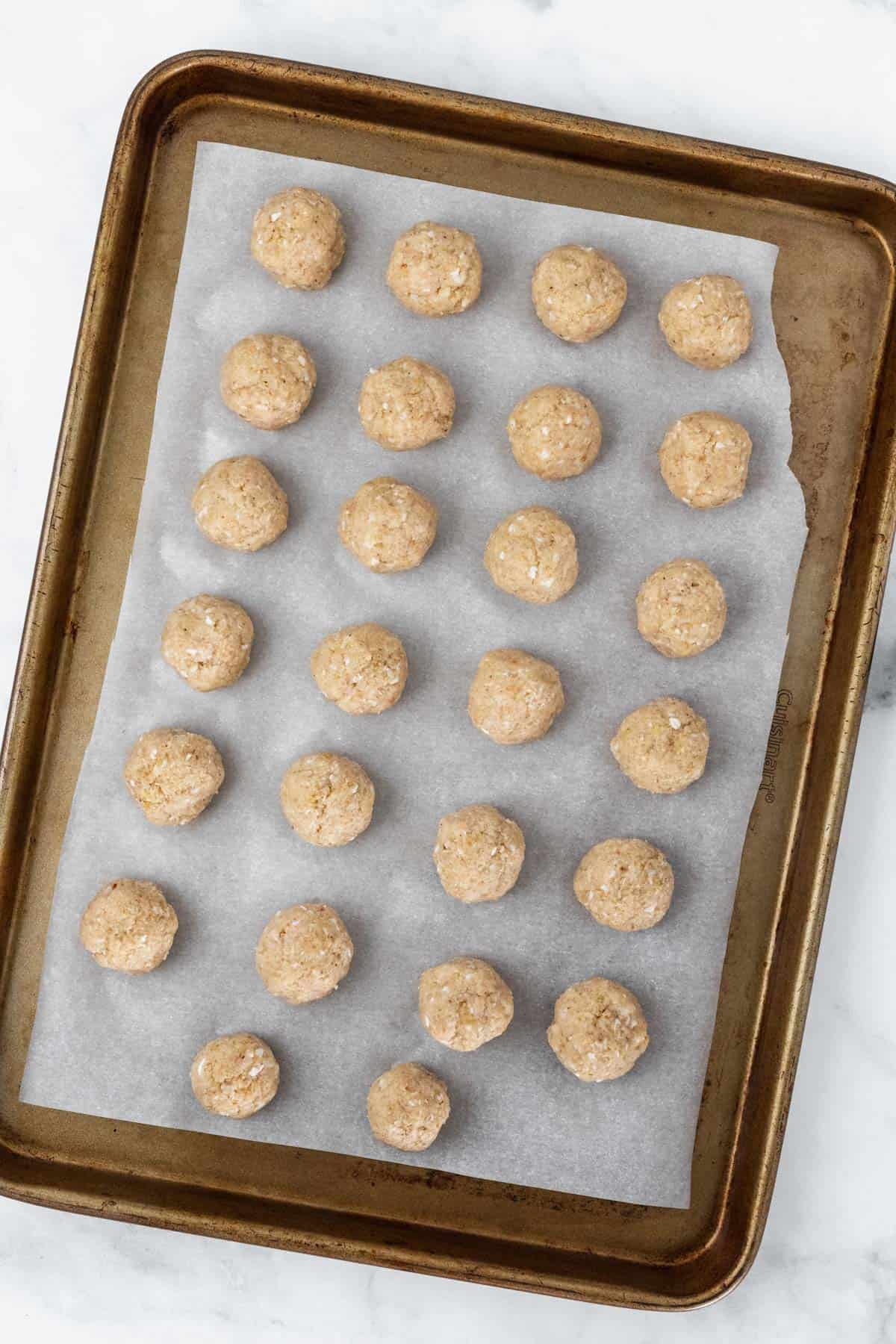Raw meatballs shaped on a baking sheet lined with parchment paper before being placed in the oven.