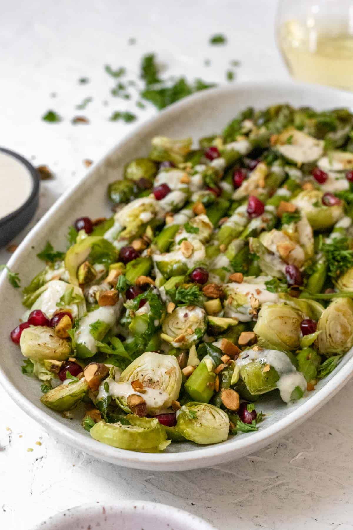 Side view of asparagus, brussels sprouts, lemon tahini sauce, pistachios, and pomegranate seeds on an oval platter.
