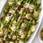 Roasted asparagus and brussels sprouts with a drizzle of lemon tahini sauce and a sprinkle of pistachios and pomegranate seeds on an oval platter.