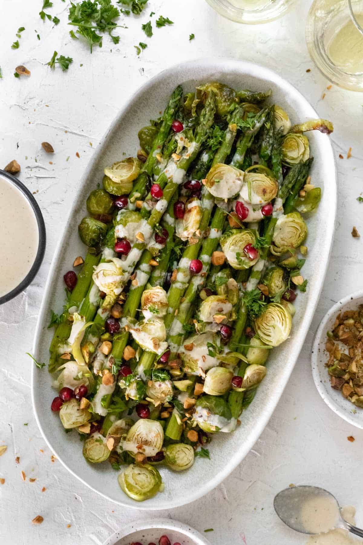 Roasted asparagus and brussels sprouts on an oval platter with bowls of extra sauce, pistachios, and pomegranate seeds around it.