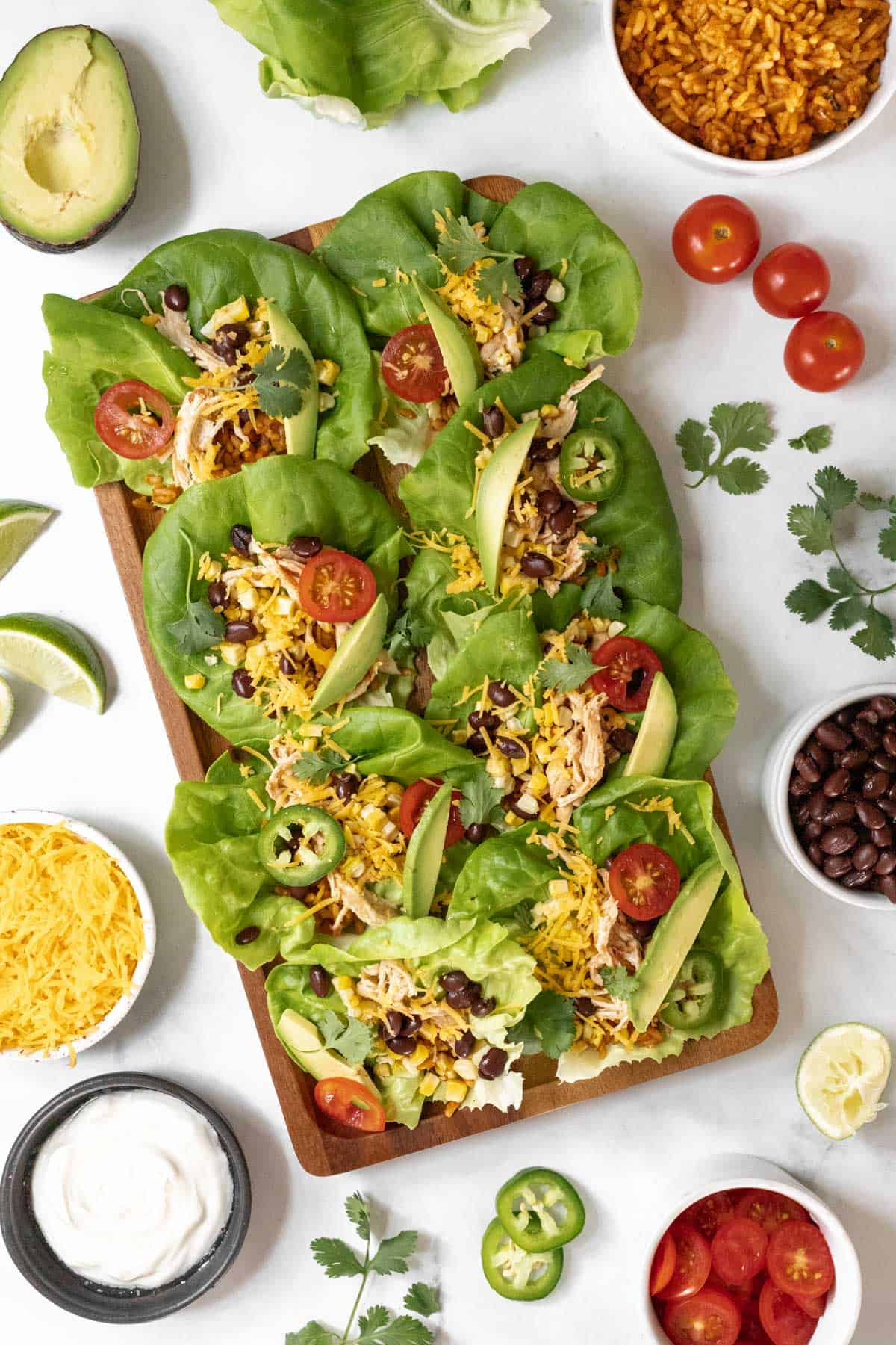 Overhead view of shredded chicken lettuce wraps on a rectangular serving platter with the taco fixings around it.