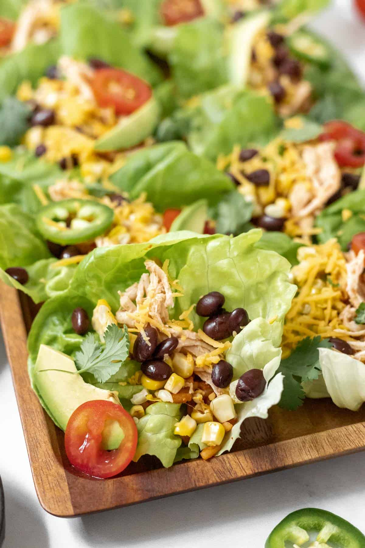 A closeup look at all the fixings inside a lettuce wrap taco: beans, corn, avocado, tomatoes, and shredded chicken.