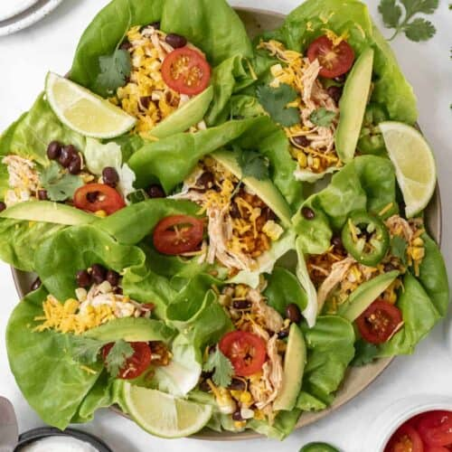 Shredded chicken taco lettuce wraps on a round platter with all the fixings around it.
