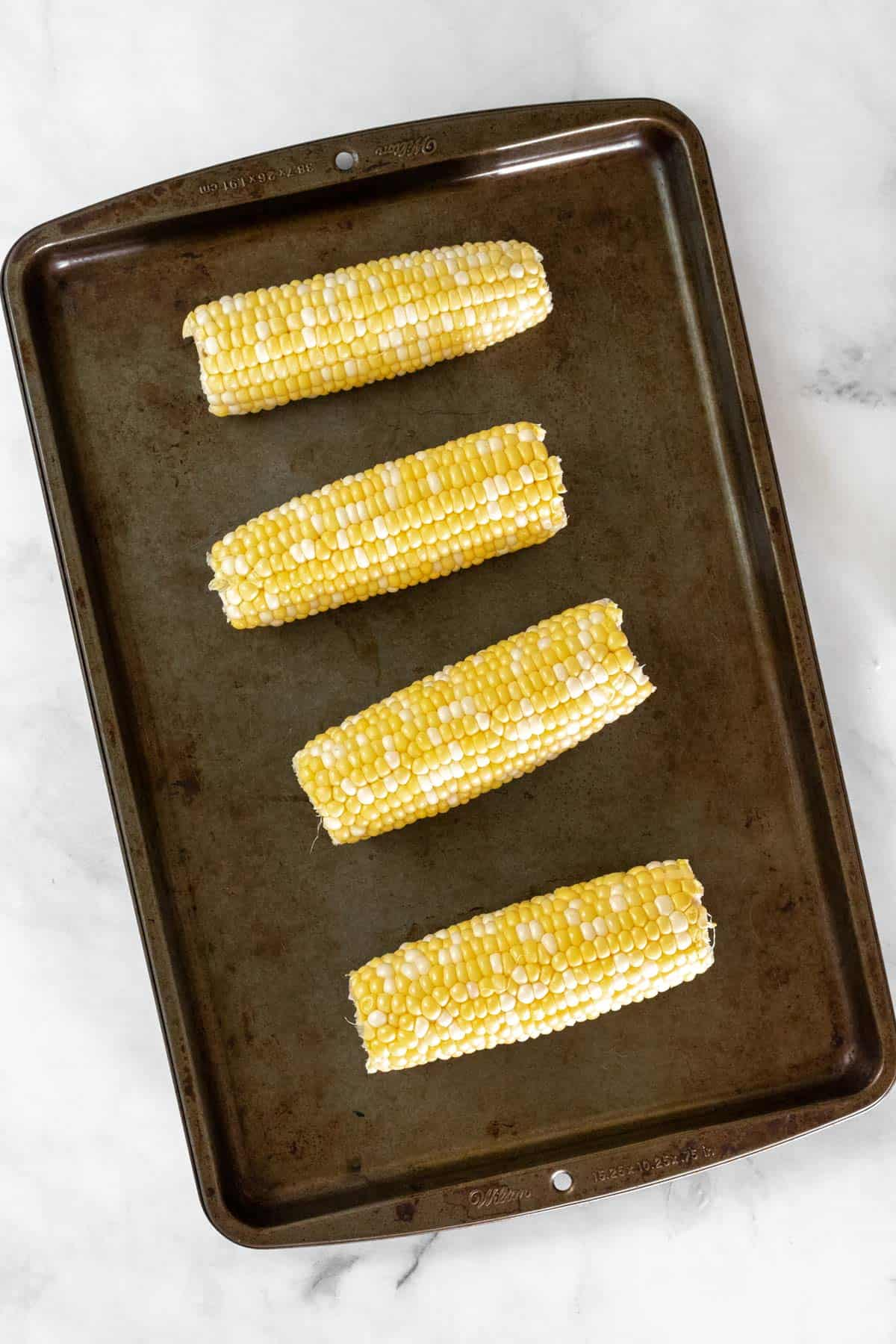 Uncooked corn on the cob on a sheet pan.