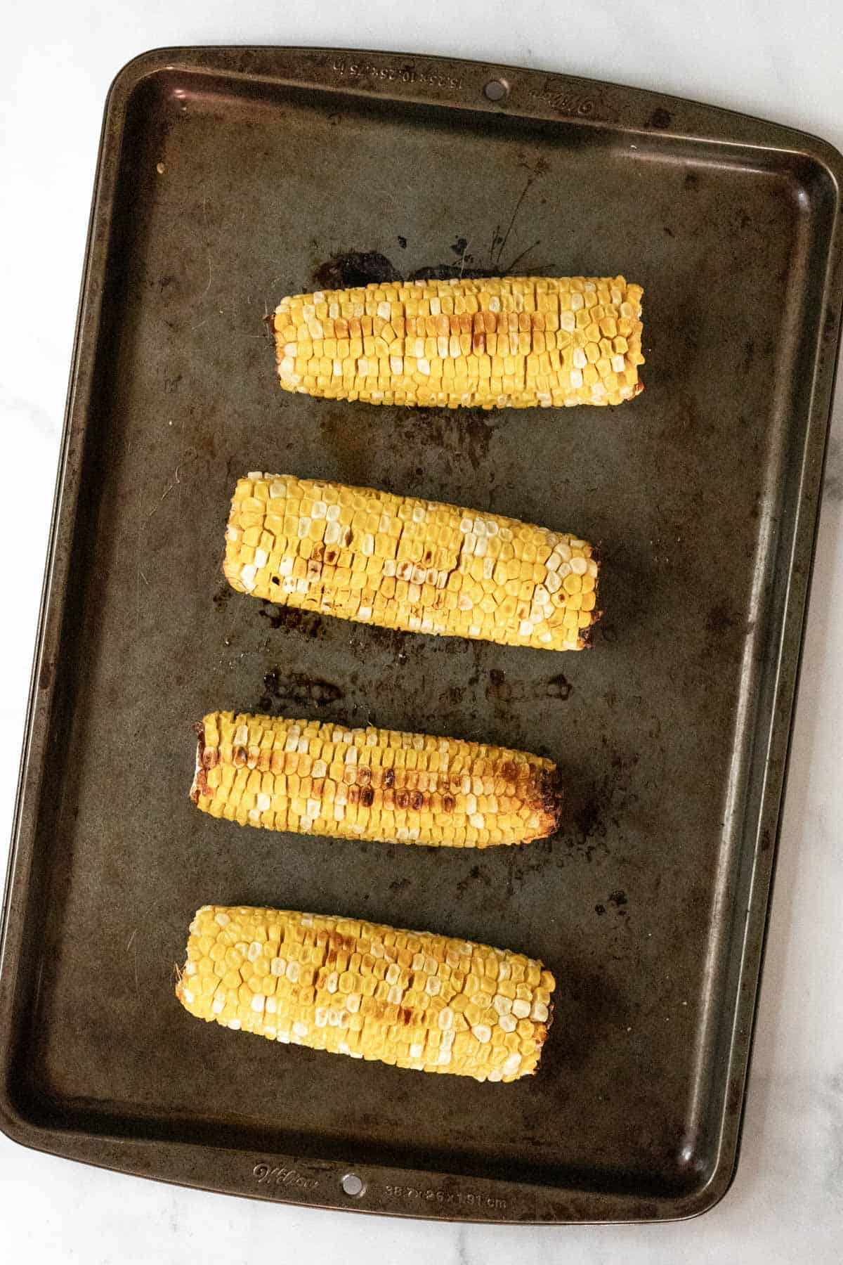 4 roasted corn on the cobs on a sheet pan.