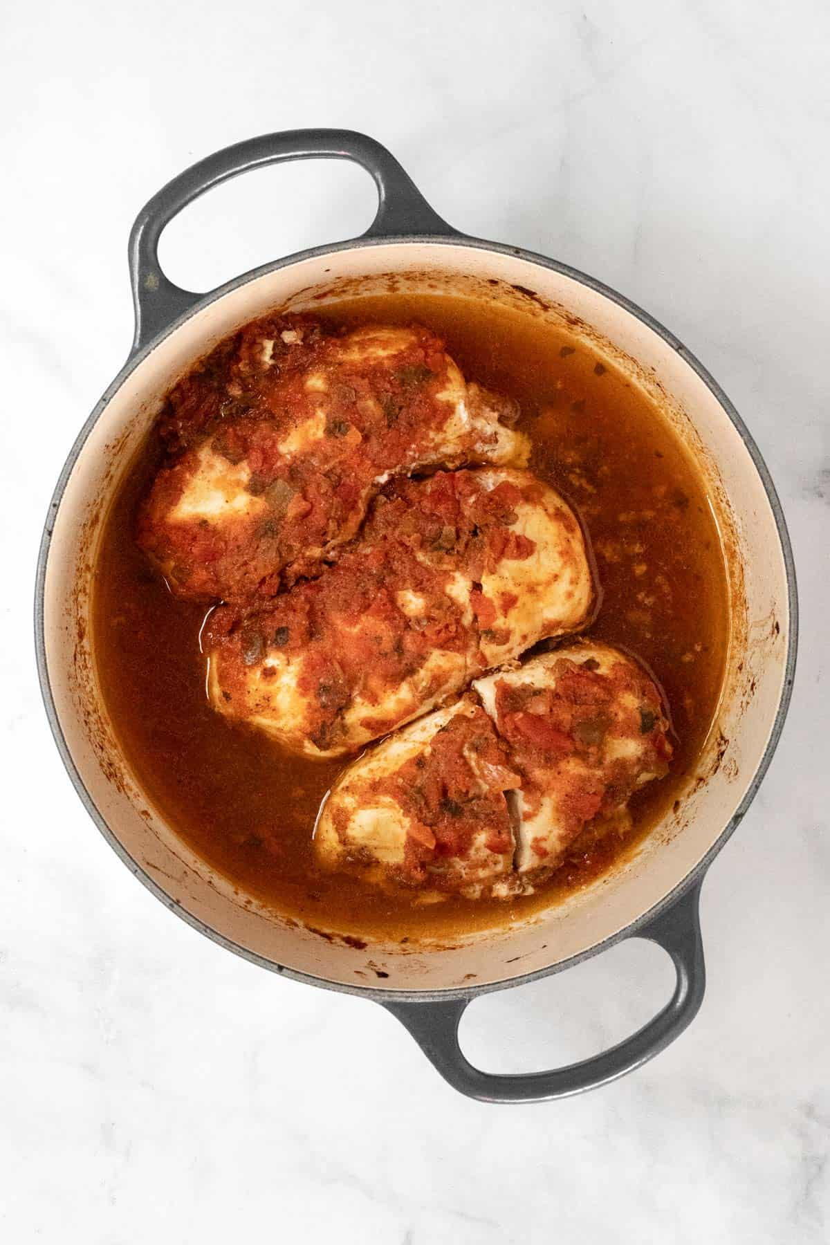 Cooked chicken breasts topped with salsa in a dutch oven.