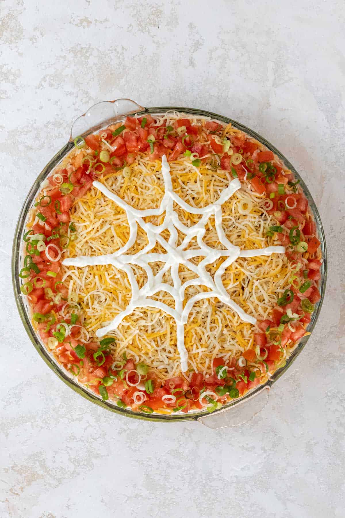 A sour cream spiderweb in progress on top of the shredded cheese.