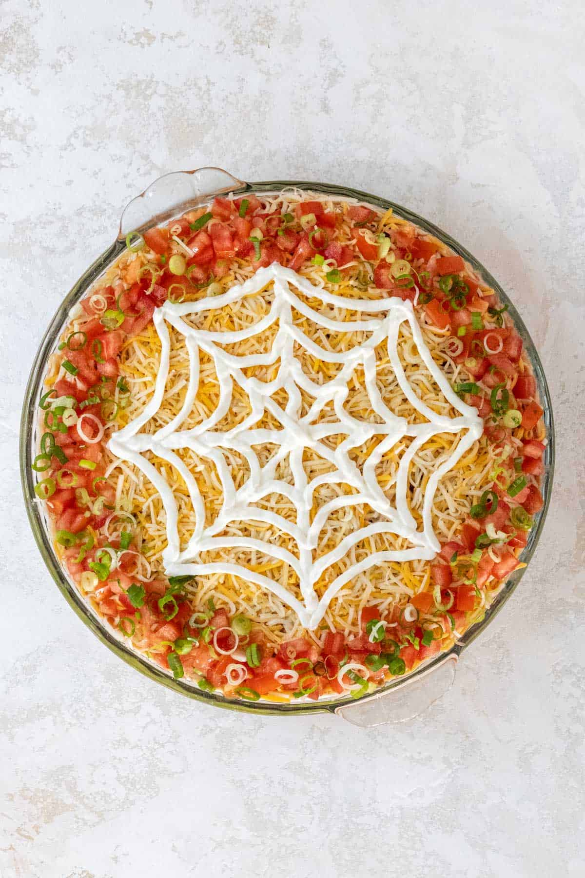A completed sour cream spiderweb on top of the shredded cheese.