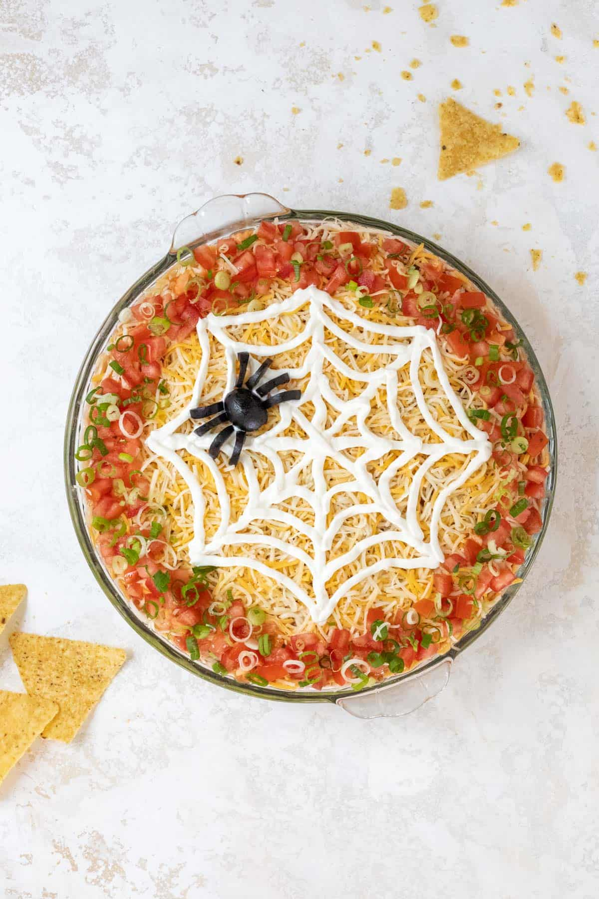 A completed Halloween 7 layer taco dip with a black olive spider on top of the sour cream spiderweb.