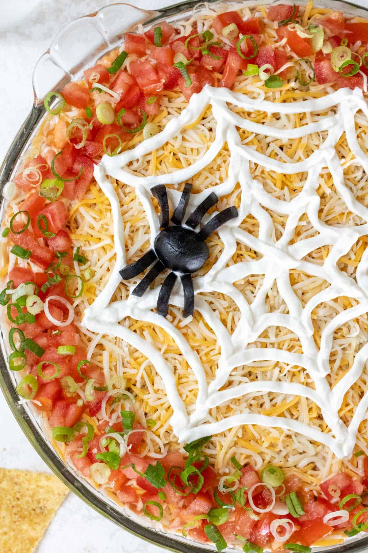 A closeup of a spider made out of black olives and a web made out of sour cream on top of Halloween taco dip.