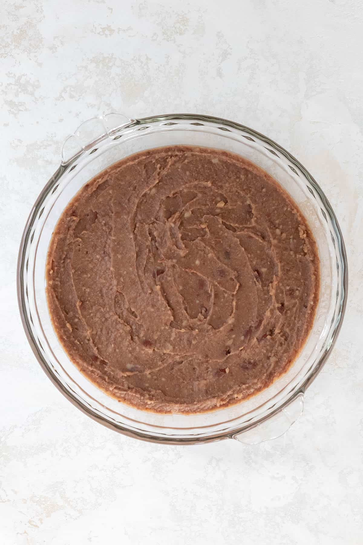 Refried beans spread out in a large pie dish.