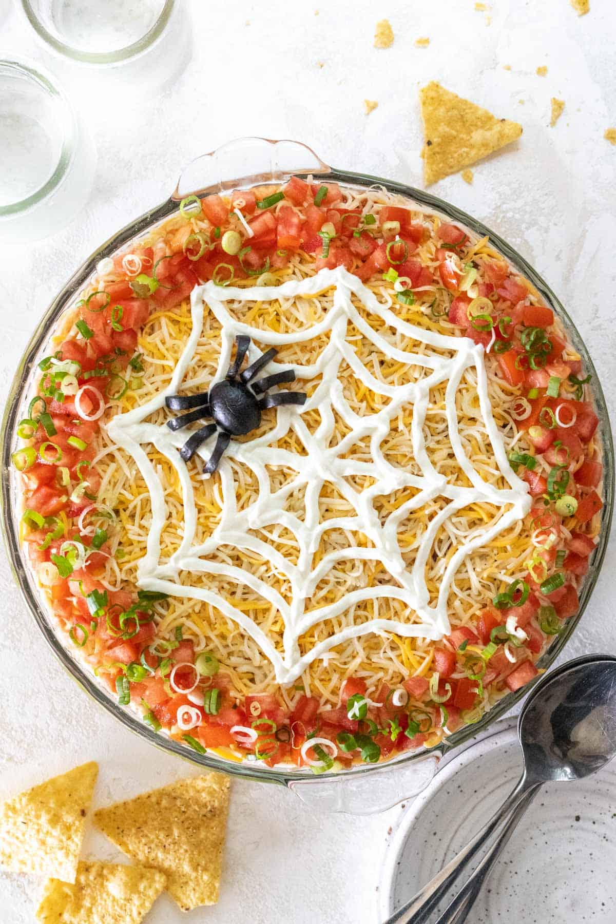 Spooky 7 layer Halloween taco dip in a large pie dish with chips around it.