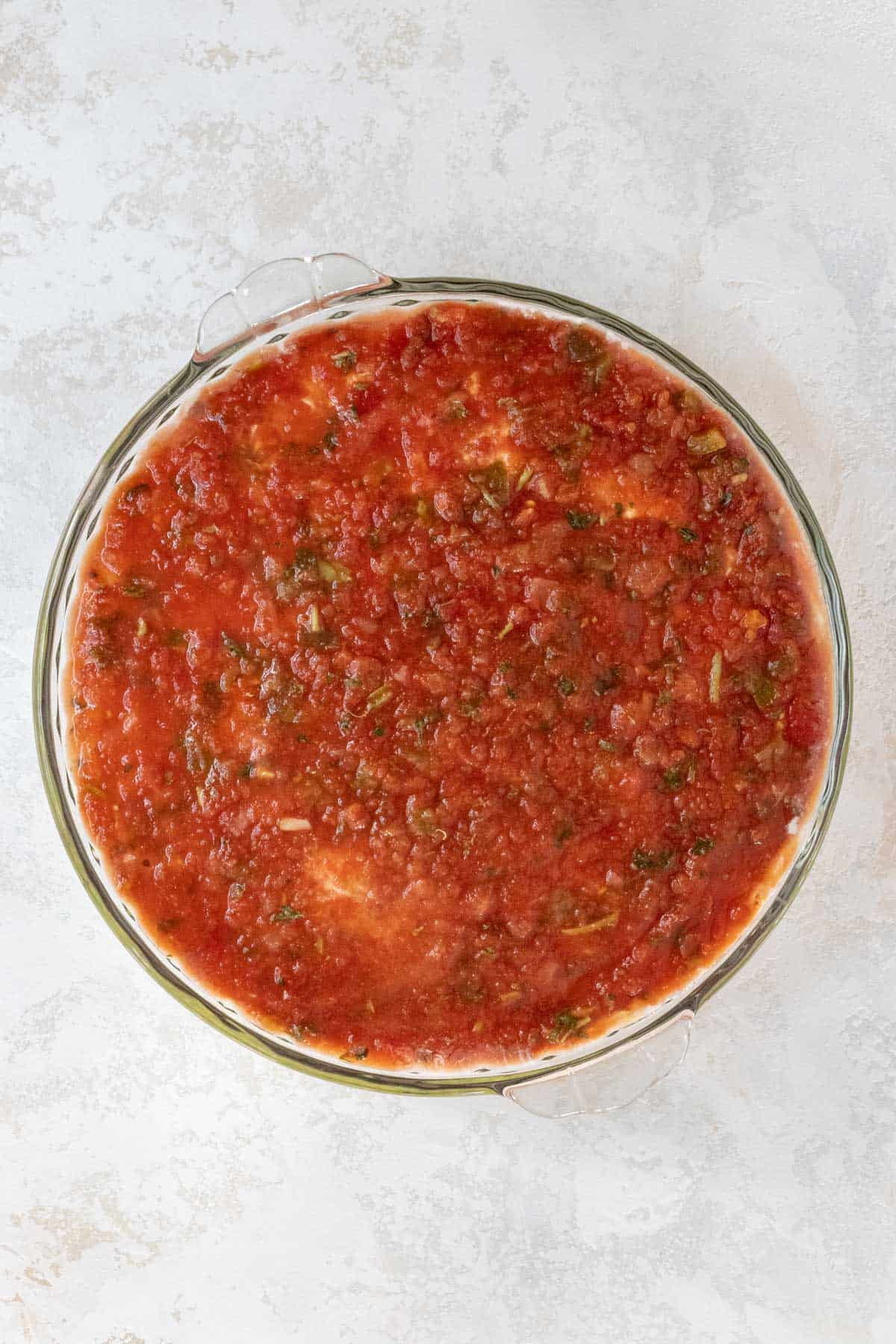 Salsa spread out over the seasoned sour cream in a large pie dish.