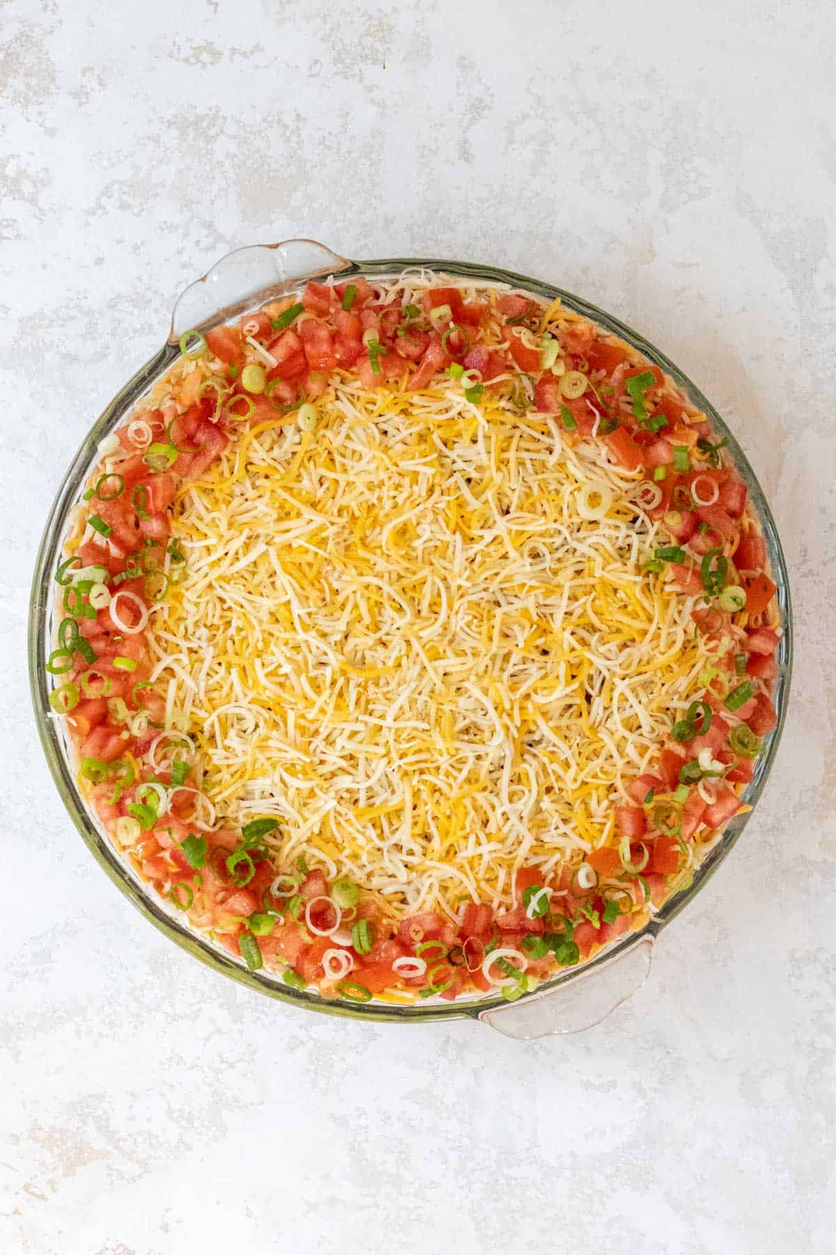 Chopped tomatoes and scallions on top of the shredded cheese and around the perimeter of a large pie dish.