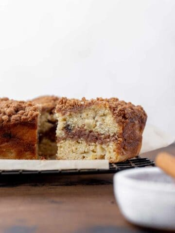 A slice of apple cider and date coffee cake with a swirl of cinnamon sugar in the middle.