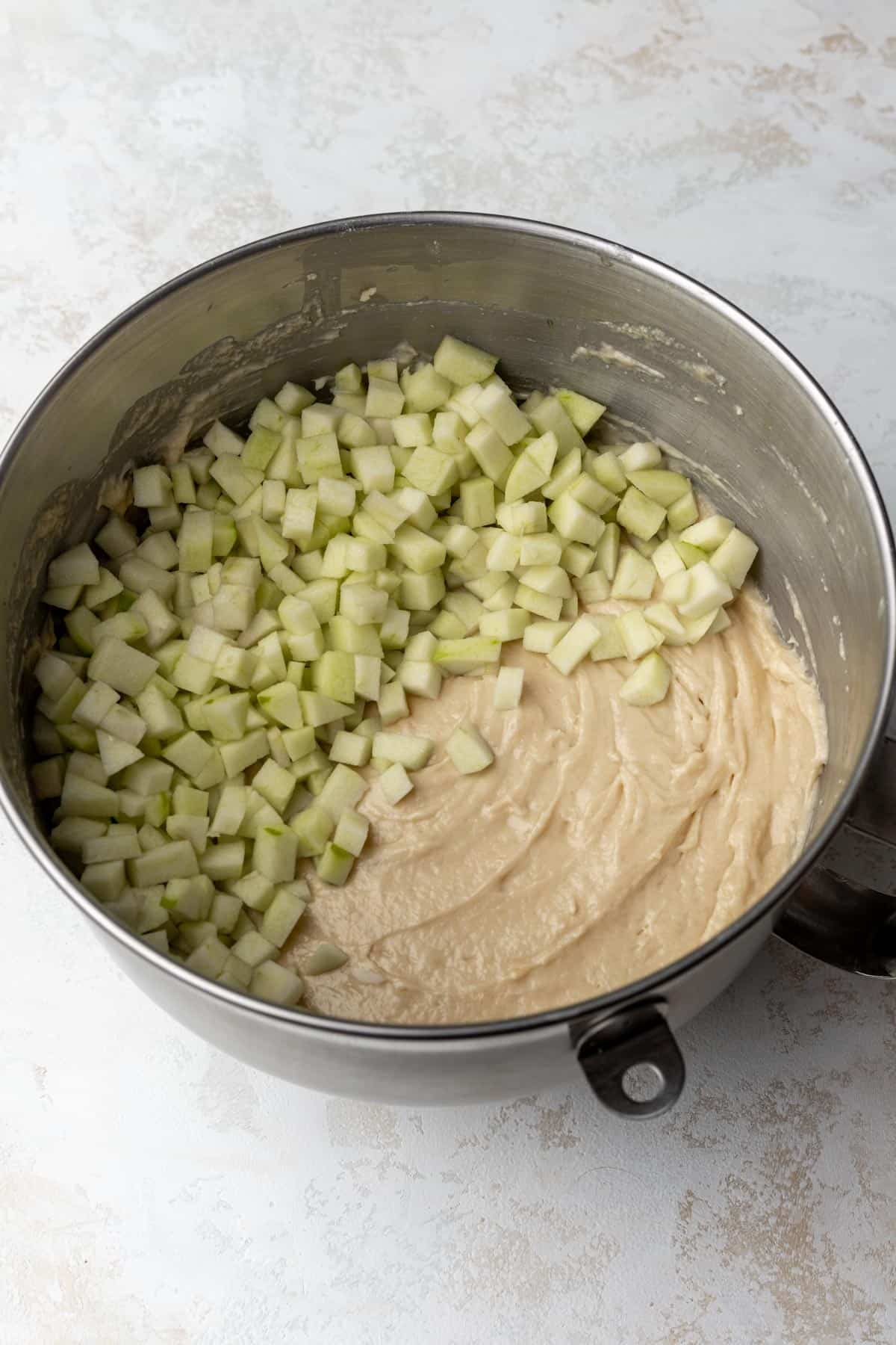 Raw apple cider cake batter with diced apples on top in a large mixing bowl.