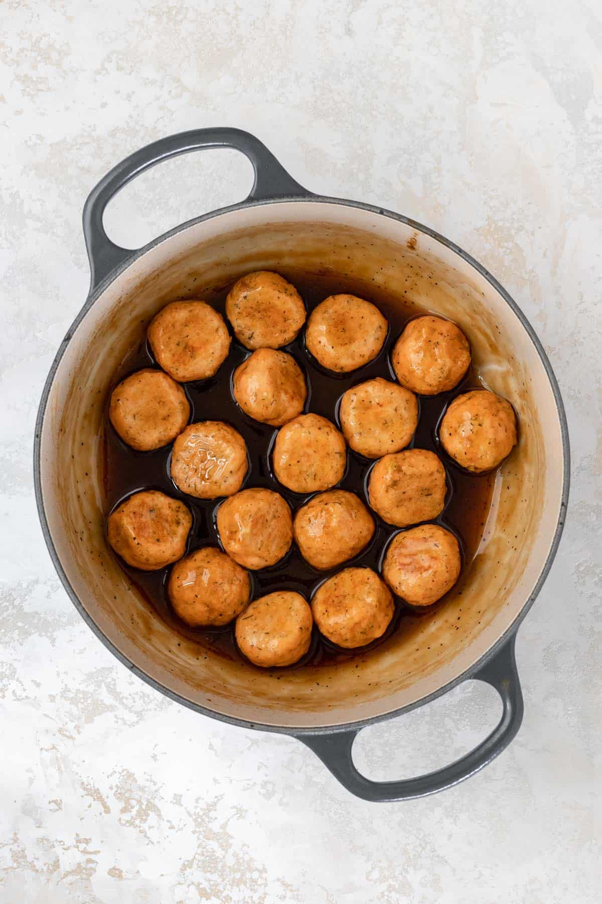 Bourbon glazed salmon meatballs in a large pot.