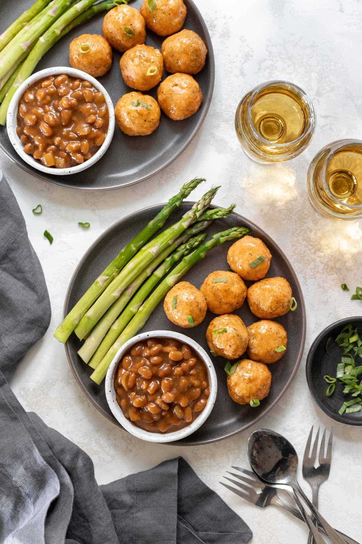 2 plates filled with honey bourbon salmon meatballs, asparagus, and baked beans.