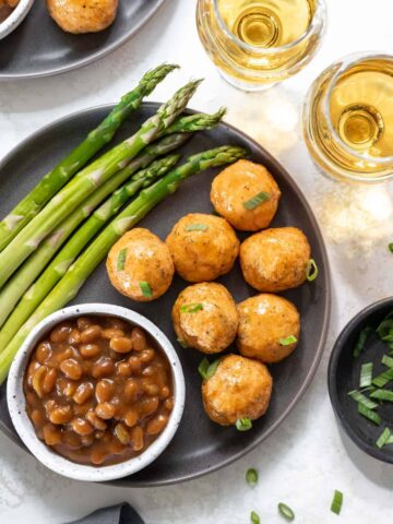 Honey bourbon glazed salmon meatballs on a gray plate with a side of asparagus and baked beans.