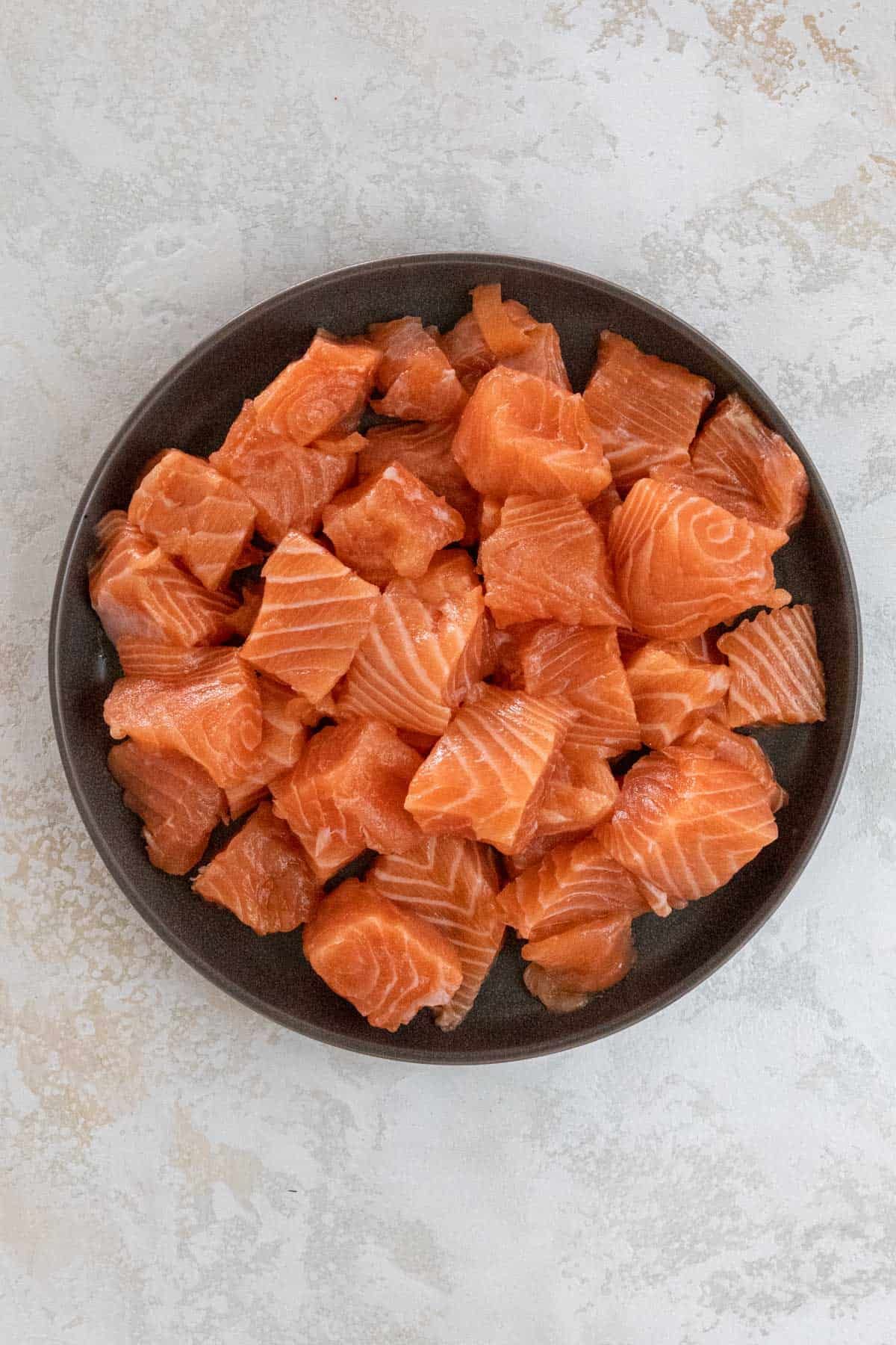 Cubed salmon in a black bowl.