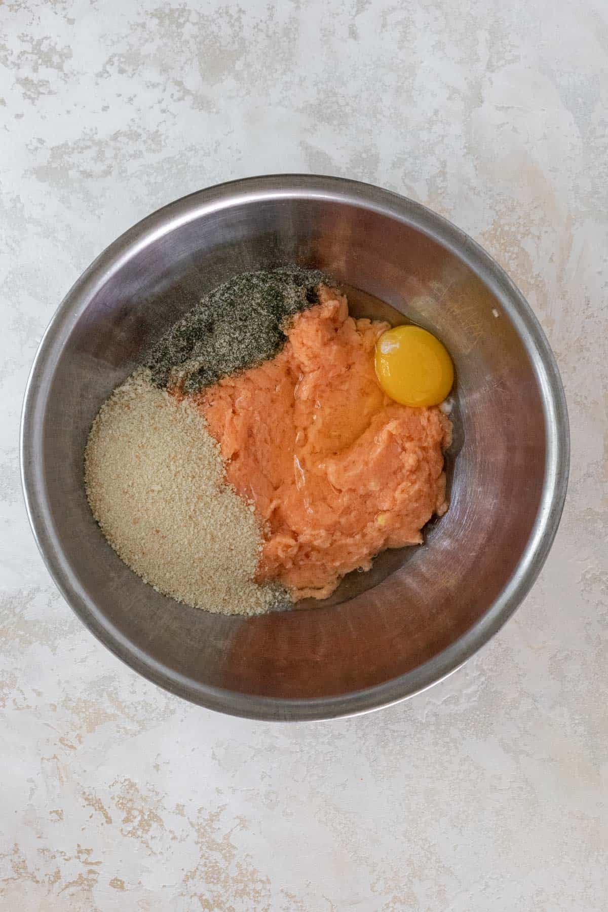 """Ground salmon"", egg, breadcrumbs, and seasonings in a metal mixing bowl."