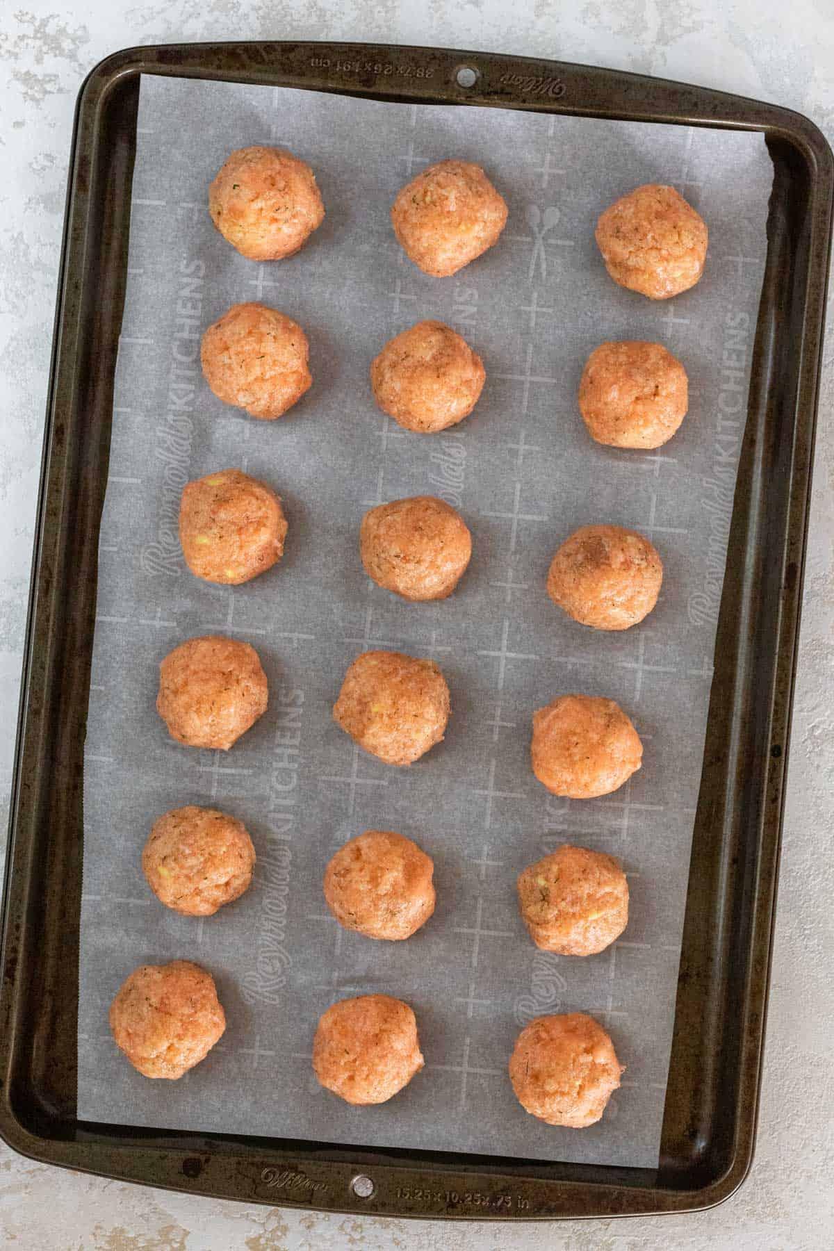 Raw salmon meatballs on a sheet pan.