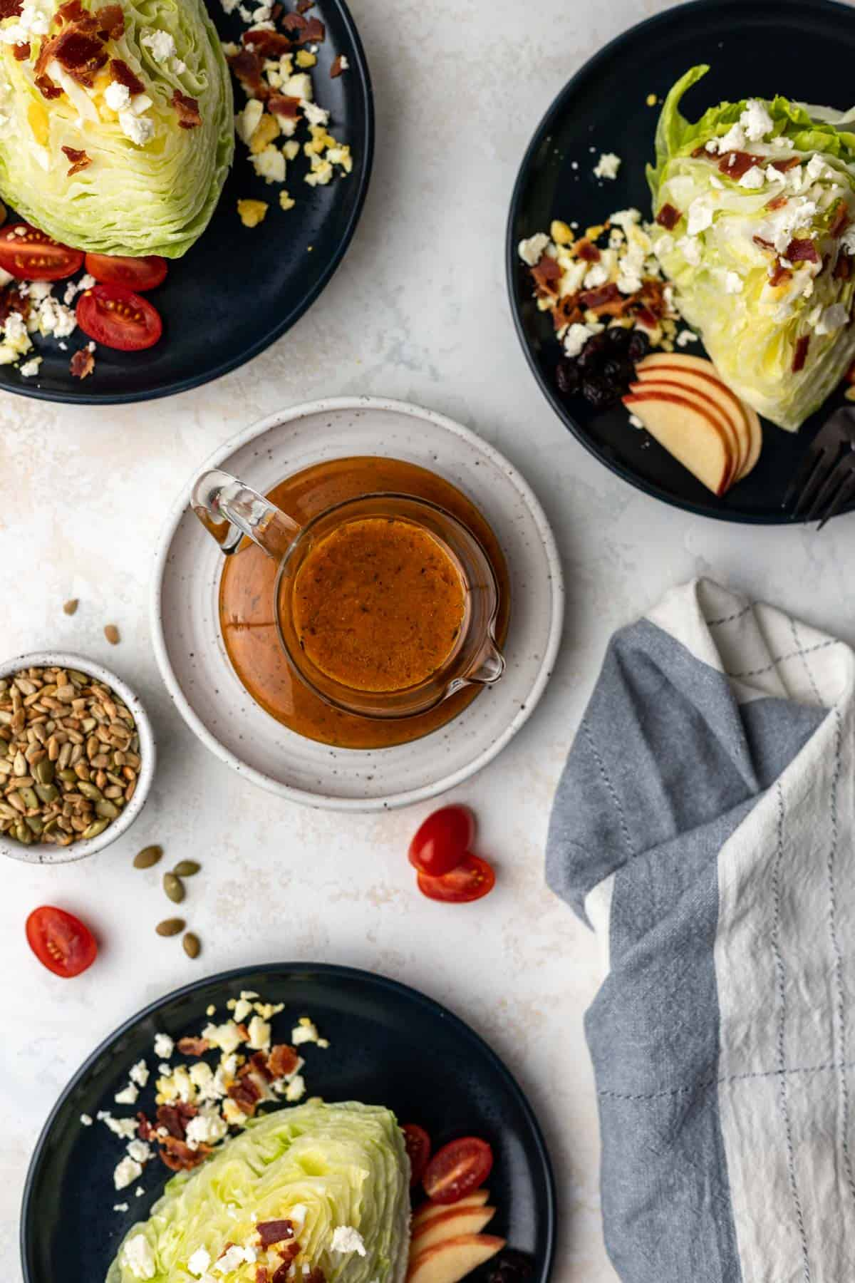 An overhead view of fall pumpkin dressing in a glass pitcher and 3 salads surrounding it.