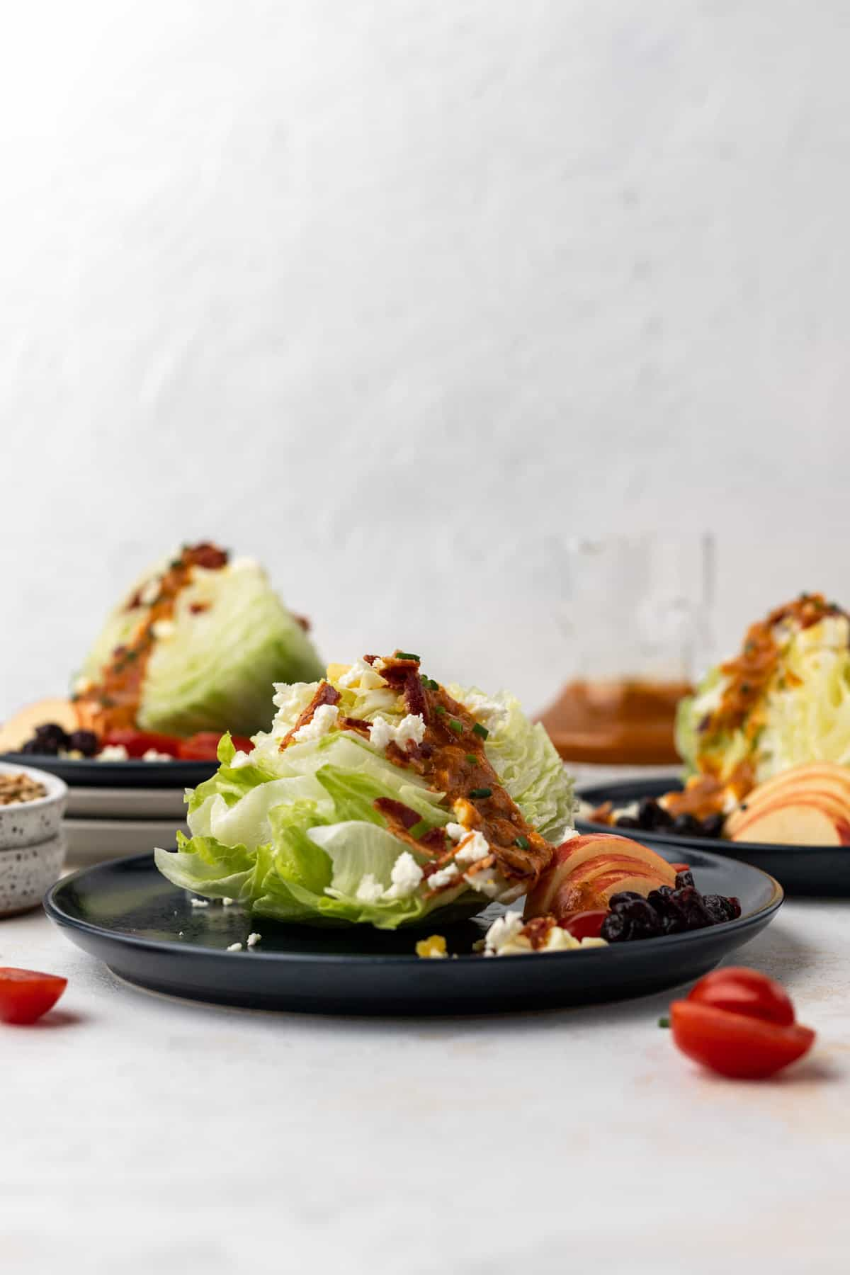 Pumpkin salad dressing drizzled over 3 wedge salads with salad toppings around them.