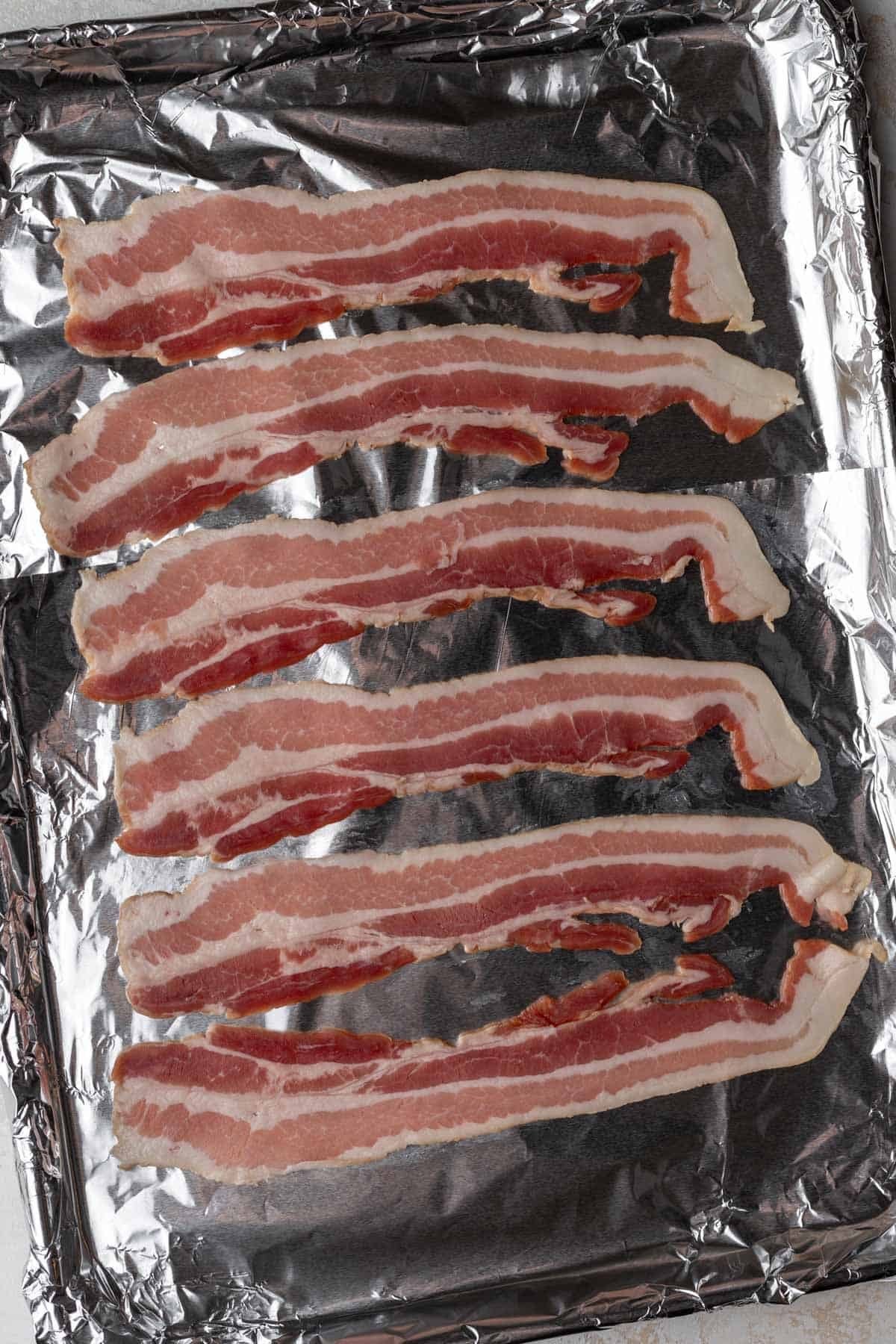 Bacon lined up on a sheet pan covered in foil.