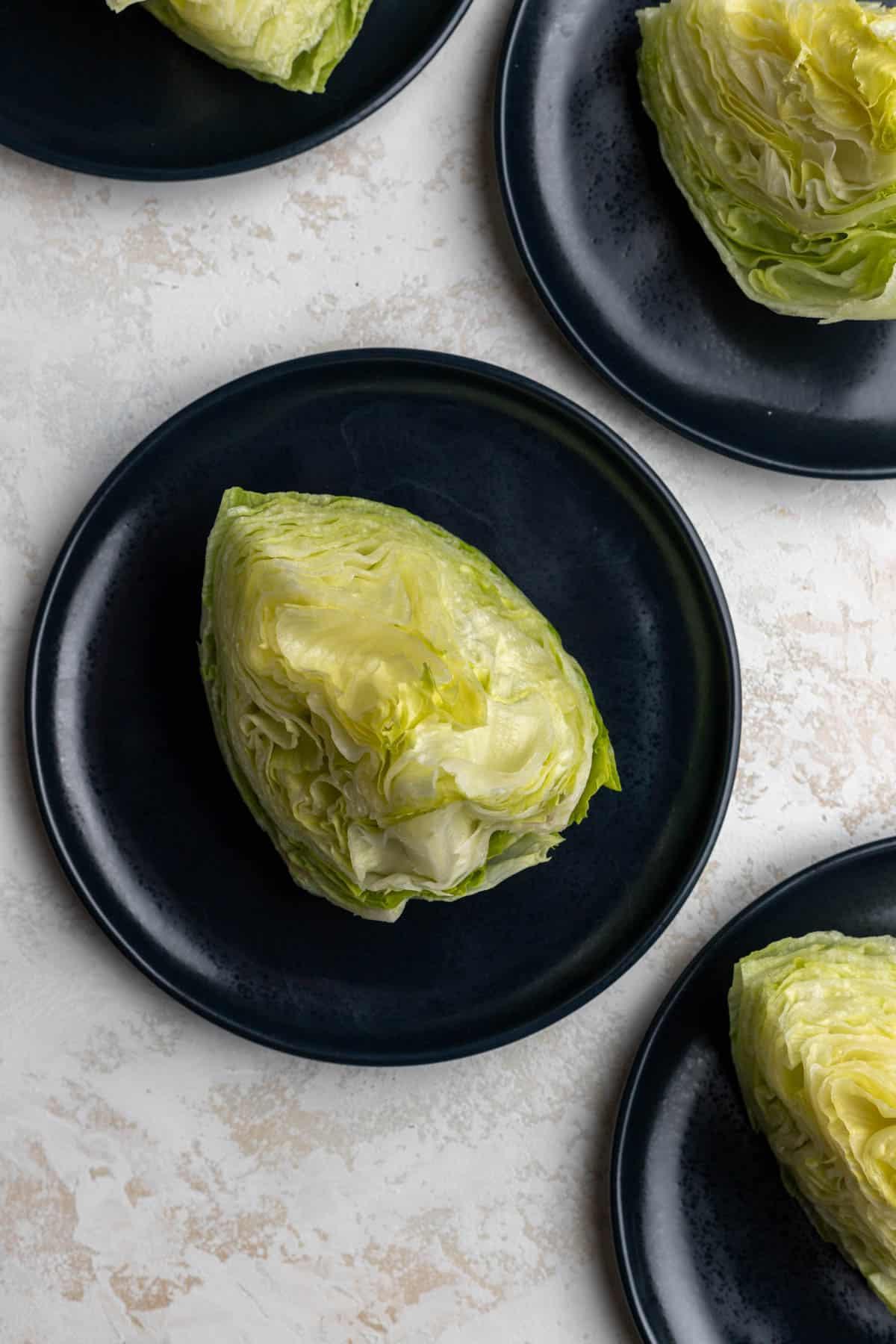 Wedges of iceberg lettuce on 4 blue plates.