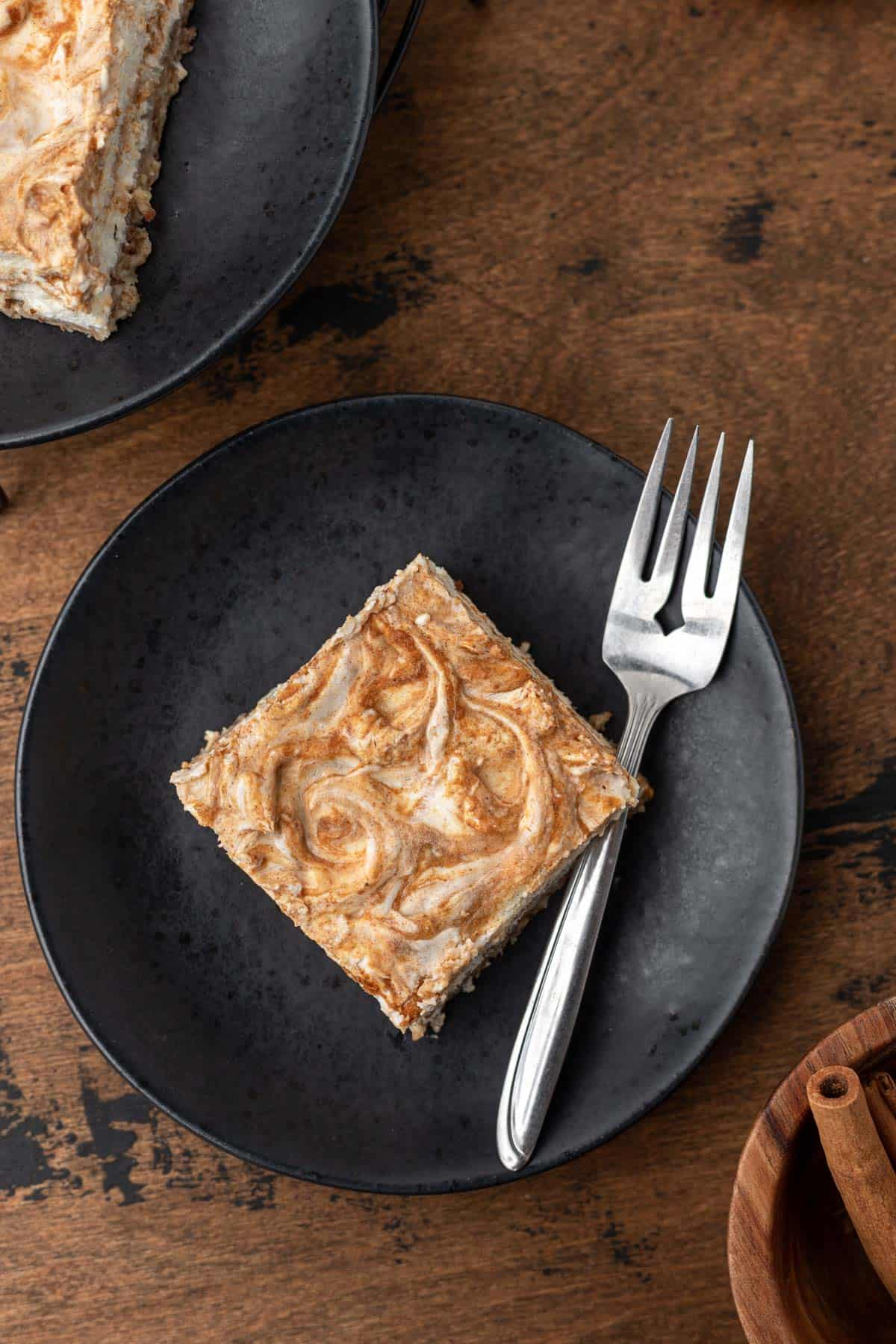 A pumpkin swirl cheesecake bar on a black plate with a fork to the side.
