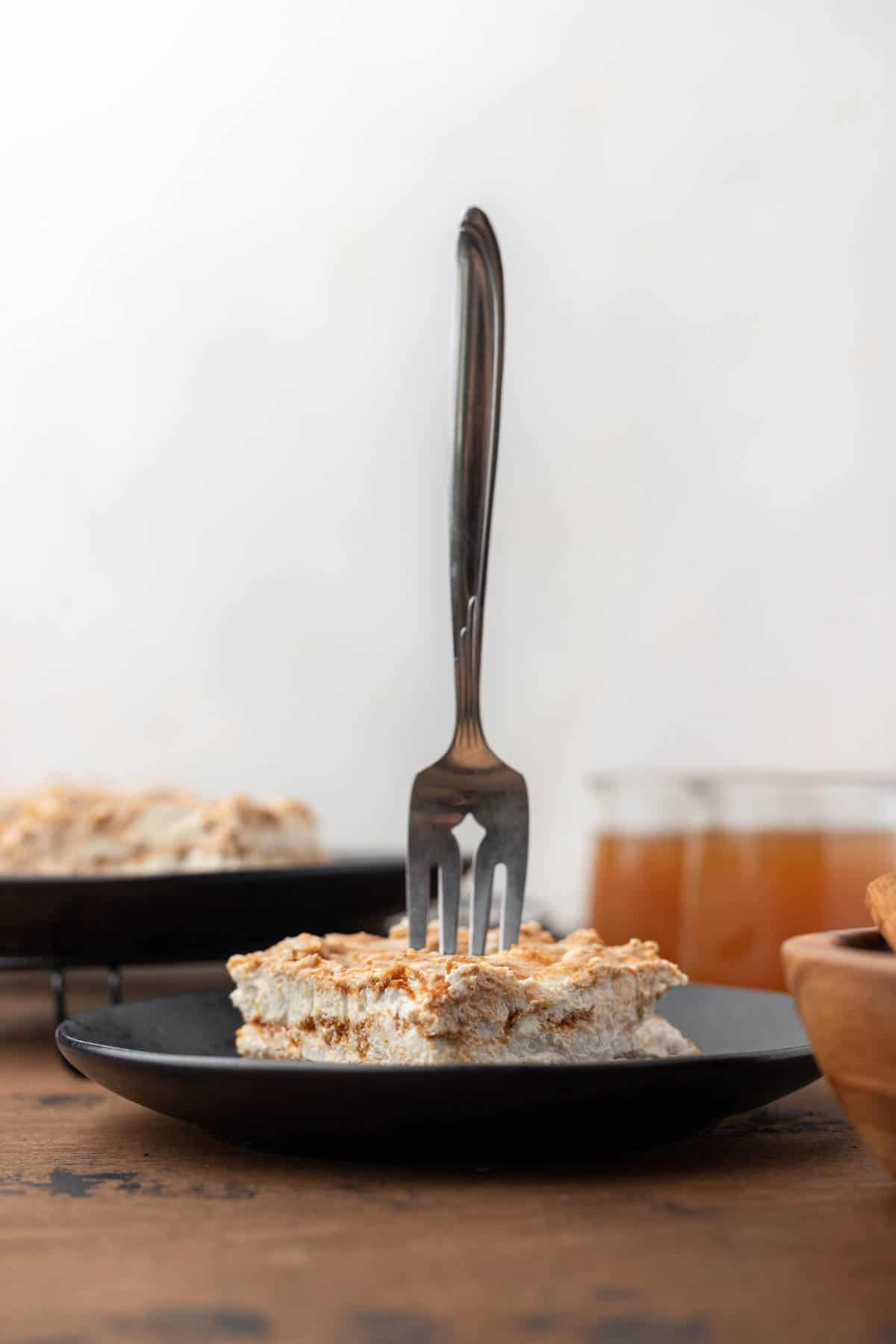 A fork sticking out of a healthy pumpkin swirl cheesecake bar with cups of apple cider next to it.
