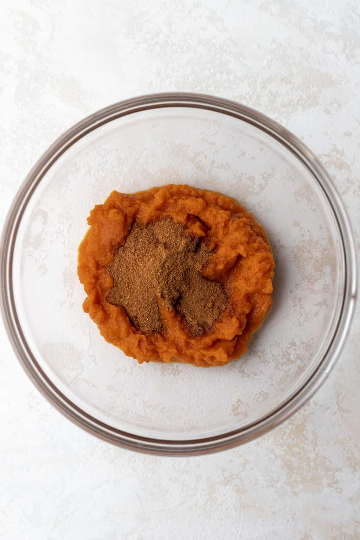 Pumpkin puree mixed with spices in a glass bowl.
